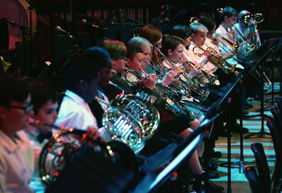 School children playing instruments on stage