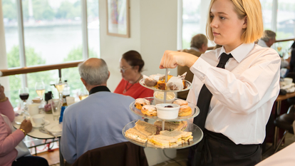 Waitress Taking Cakes and Sandwiches Around