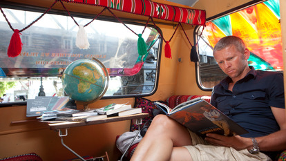 Man reading Book in Caravan at London Literature Festival