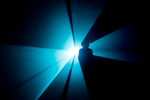 Woman standing in Blue Light Beam by artist, Anthony Mccall at Hayward Gallery