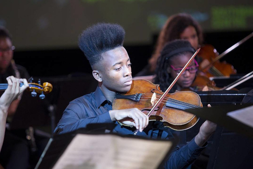 A young boy playing the violin at Chineke Juniors