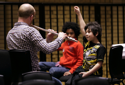 Children with man playing instrument