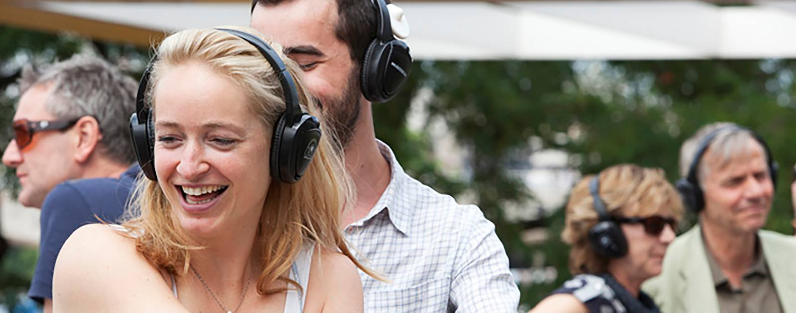 A happy couple participate in an event wearing headphones at the Southbank Centre
