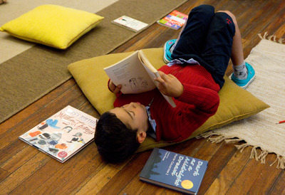 A young boy reads books in The Poetry Library